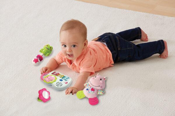 Auf dem Bauch liegendes Baby mit Produkten aus dem VTech Babys Geschenkset
