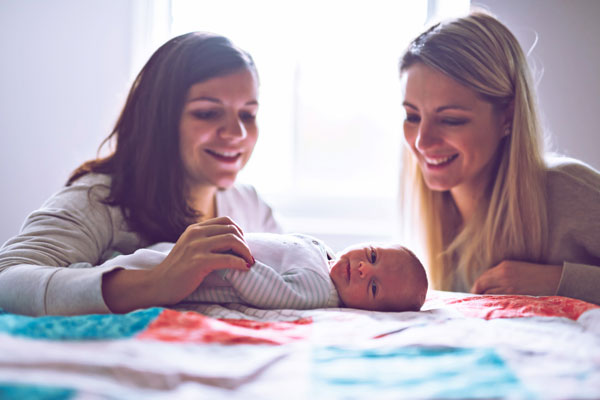 Zwei Frauen schauen lachend ein liegendes Baby an
