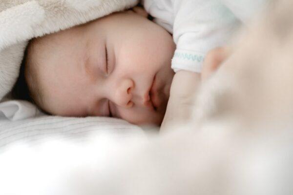 Baby liegt auf der Seite zugedeckt und schläft