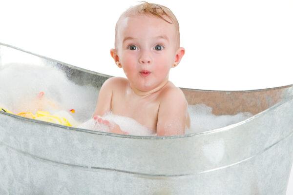 Süßes 1 jähriges kleines Mädchen guckt überrascht und hat Spaß in der Badewanne